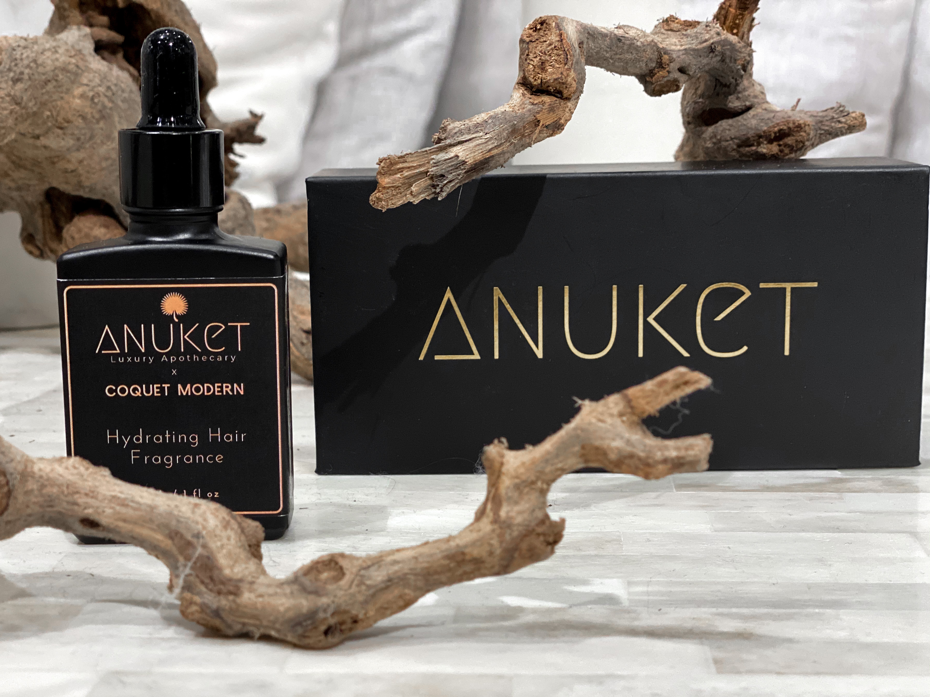 Bottle of Anuket Luxury's Hydrating Hair Fragrance on table next to black packaging keep sake box, with wood branches