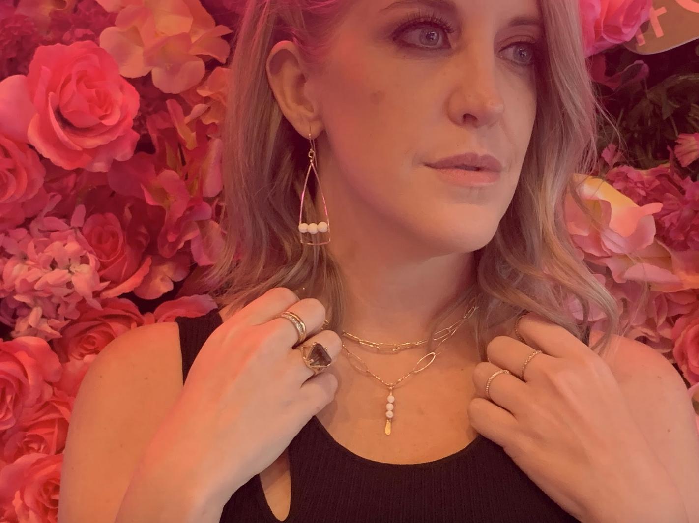 Ashlee Dozier wearing Anuket x James & Jezebelle's fragrance diffusing demi-fine jewelry piece Nile earrings