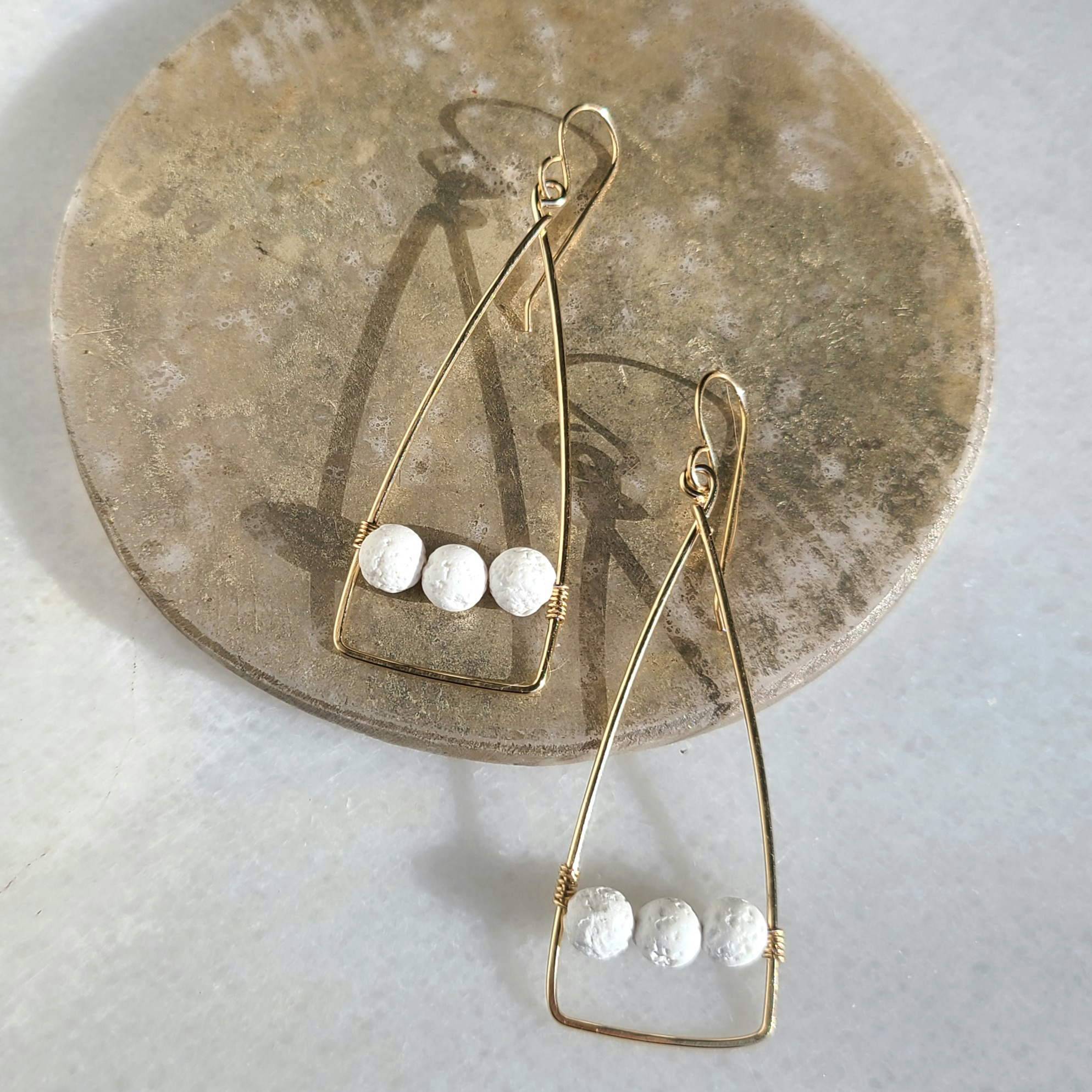 Anuket x James & Jezebelle Hedjet Earrings demi-fine gold triangle hoops with white lava rock stones for diffusing fragrance jewelry
