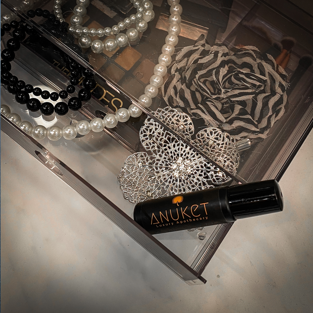 Bottle of Anuket papyrus oil roll-on fragrance perfume in a jewelry box with pearl necklace and lapel pin