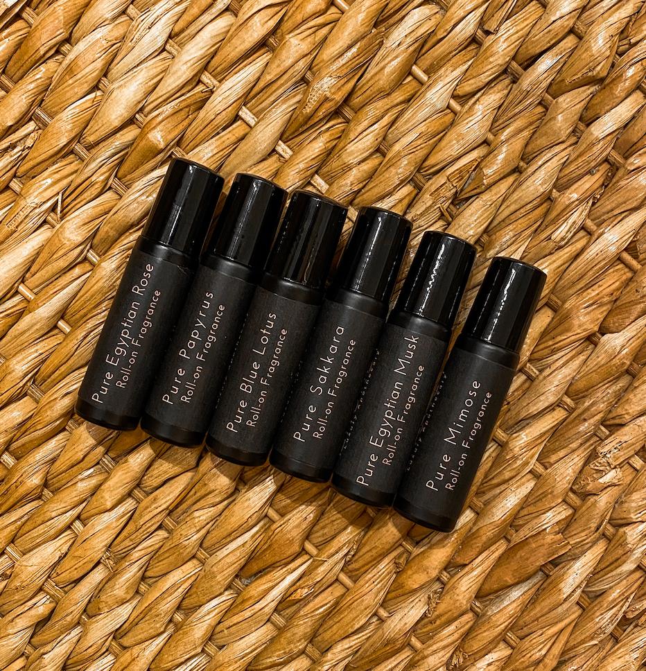 Anuket's six Egyptian essential oil fragrances bottles lying on a wicker background