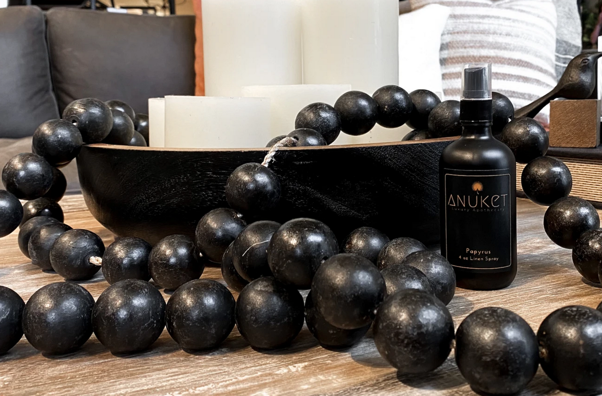 Bottle of Anuket Luxury Apothecary's Papyrus Linen Spray on a table with black blessing beads