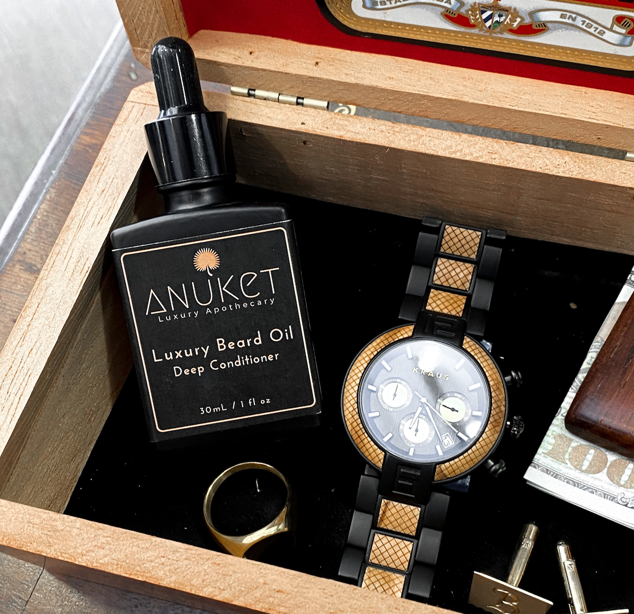 Bottle of Anuket Luxury Beard Oil in a men's valet box with ring, watch, and cufflinks