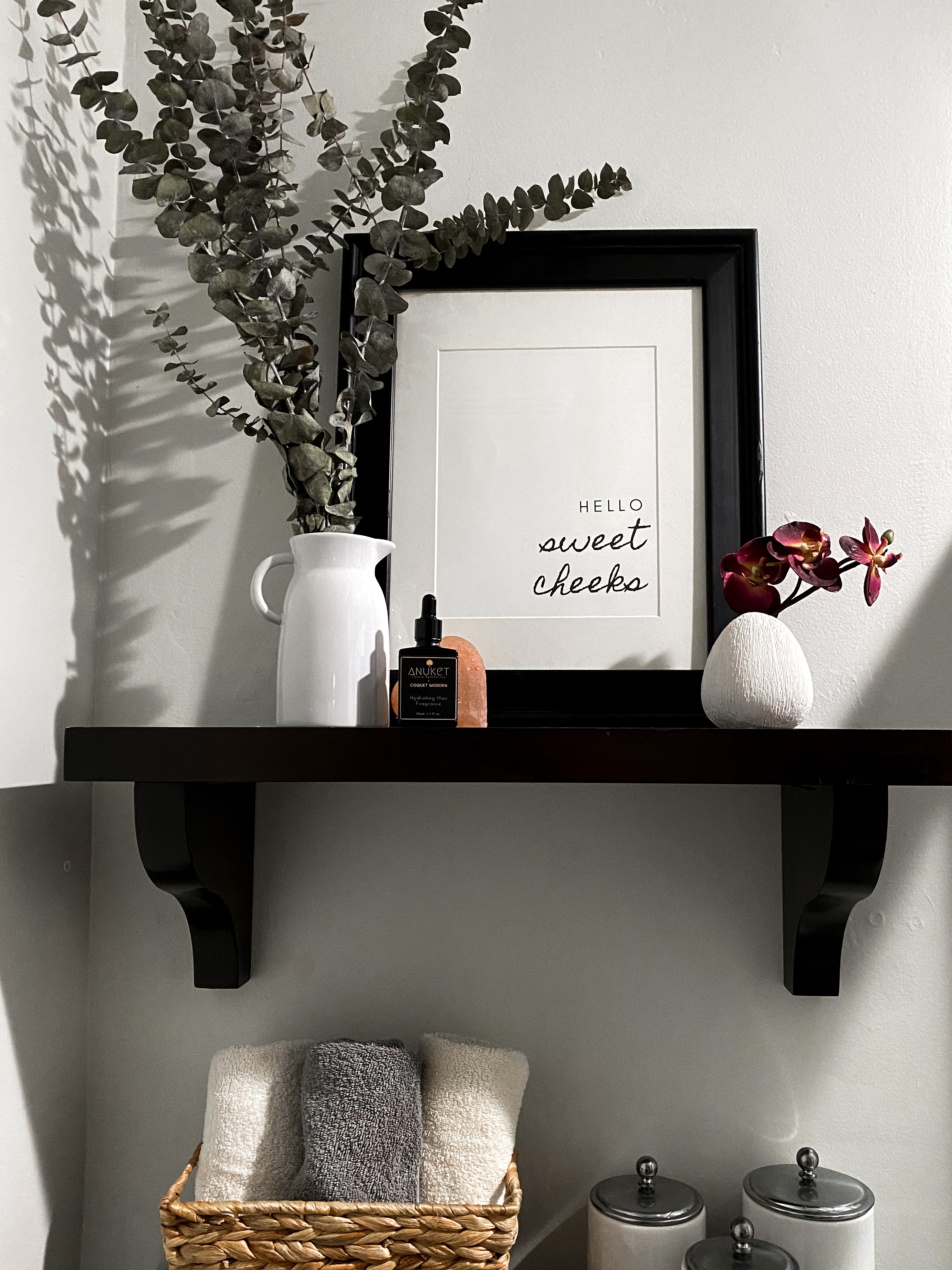 Bottle of Hydrating Hair Fragrance on bathroom shelf with eucalyptus and picture frame