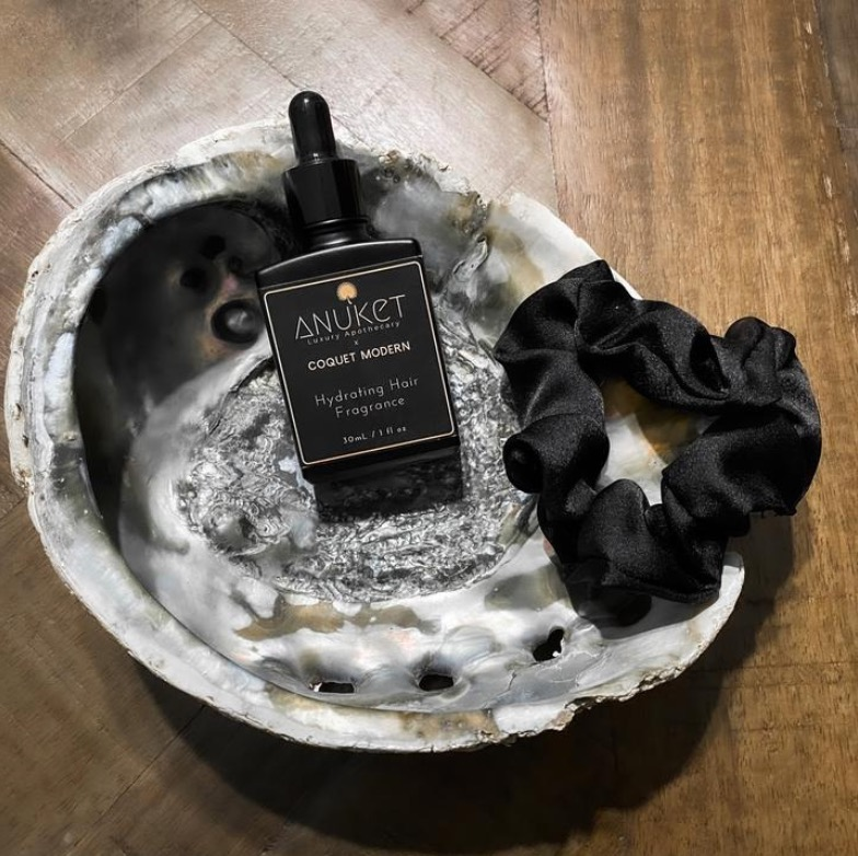 Anuket Luxury bottle of Hydrating Hair Fragrance in dish with Anuket silk hair tie