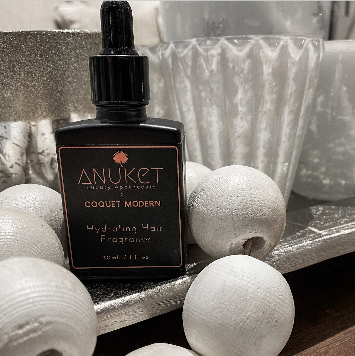 Anuket x Coquet Modern Hydrating Hair Fragrance black bottle sitting next to white blessing beads and silver candle holders