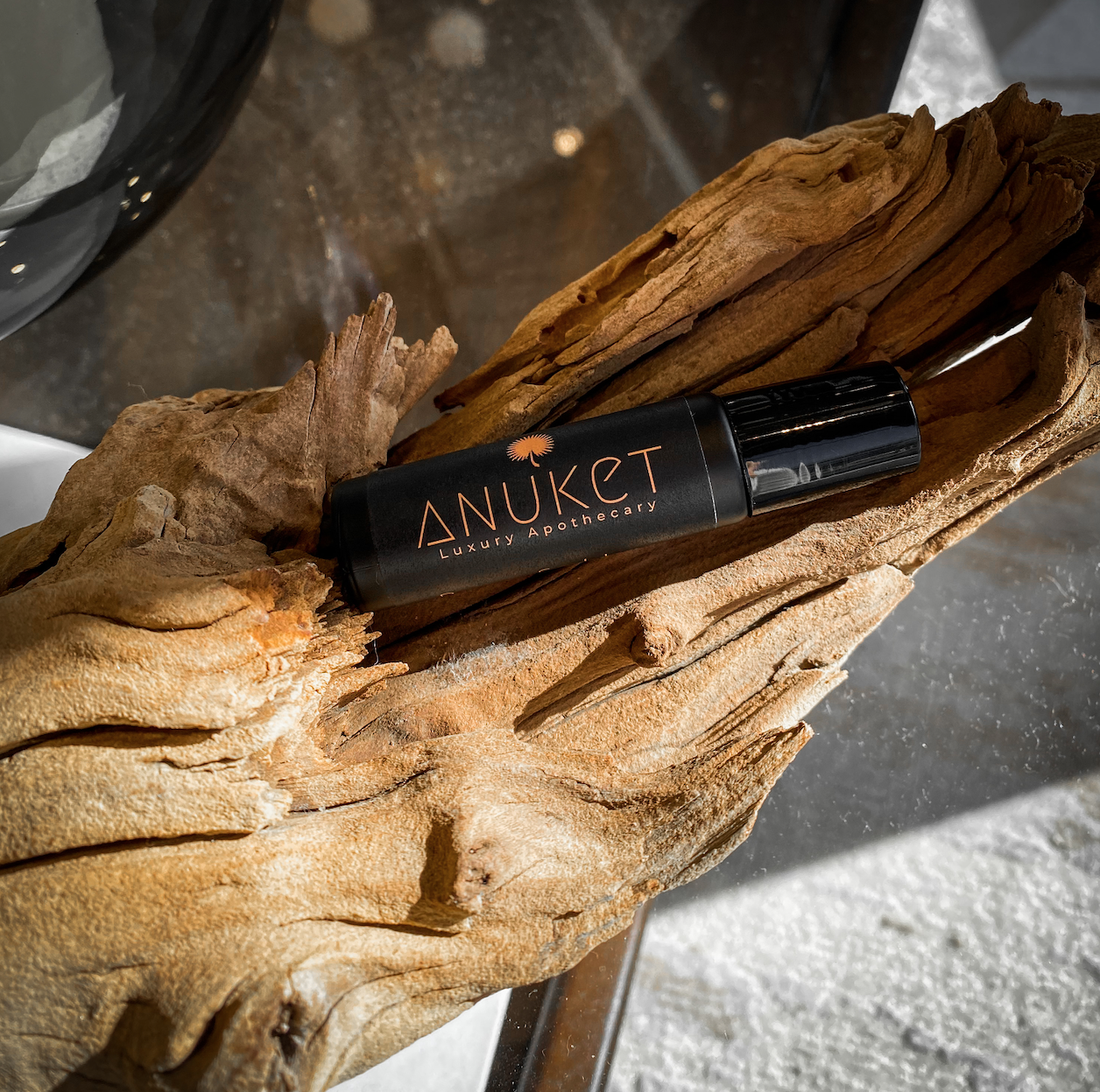 Anuket Luxury Pure Papyrus roll on fragrance oil in black bottle on a piece of driftwood on a glass table