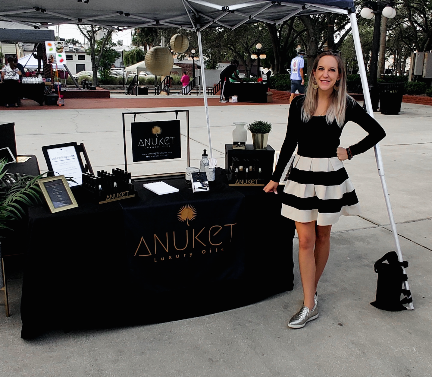 Ashlee Dozier at pop up event with table of Anuket Luxury Apothecary products