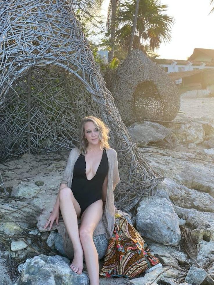 Anuket owner, Ashlee Dozier in sitting on rocks in Tulum, wearing a black swimsuit