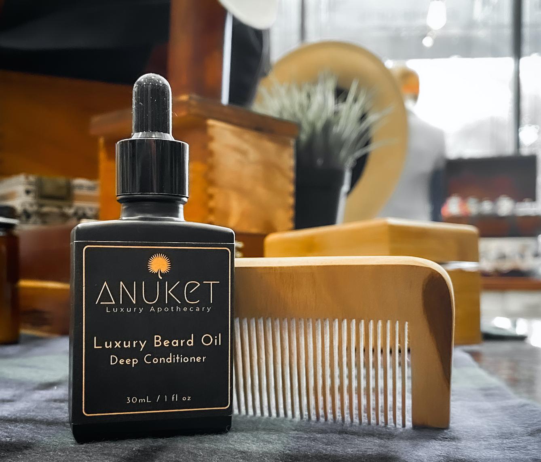 Black Bottle of Anuket's Luxury Beard Oi next to a wooden beard comb