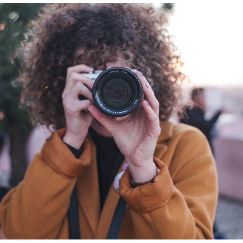 Woman photographer holding camera lens to the camera