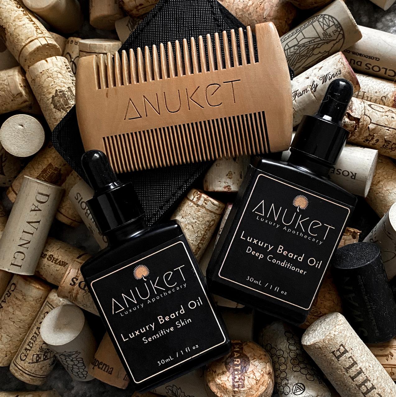 Anuket's Two Luxury Beard Oil Formulas and Sandalwood Beard Comb lying on a background of wine corks