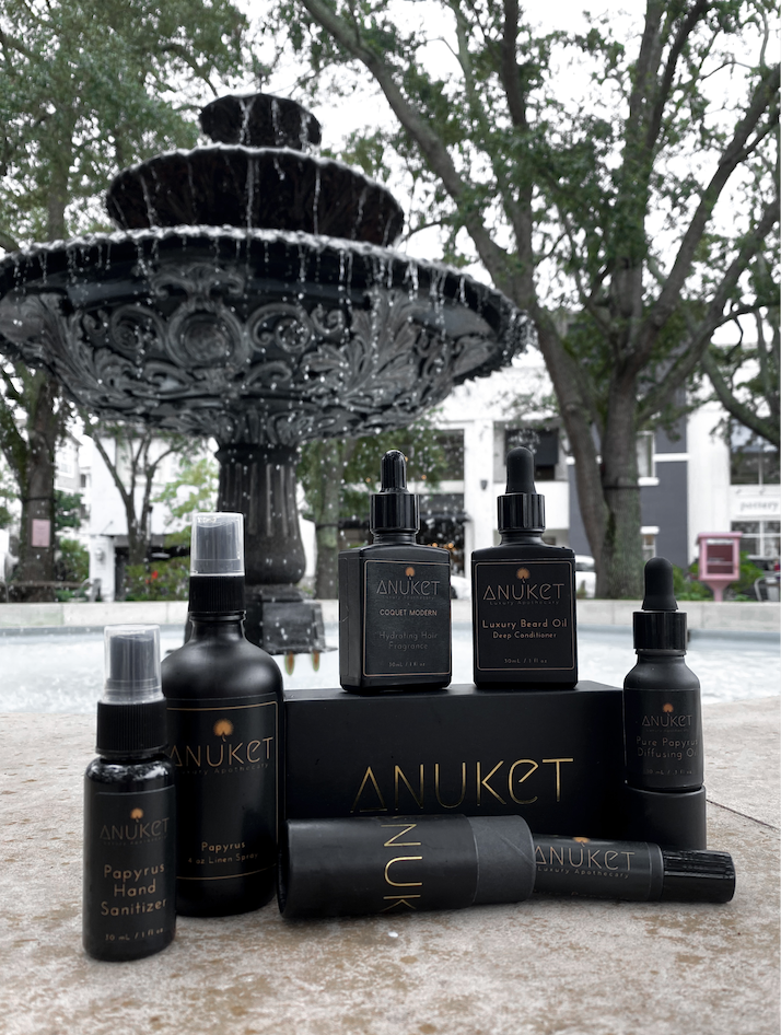 Box of Anuket Fragrance Sampler Set with papyrus, lotus, musk, mimose, sakkara, and rose oil on a white faux fur blanket