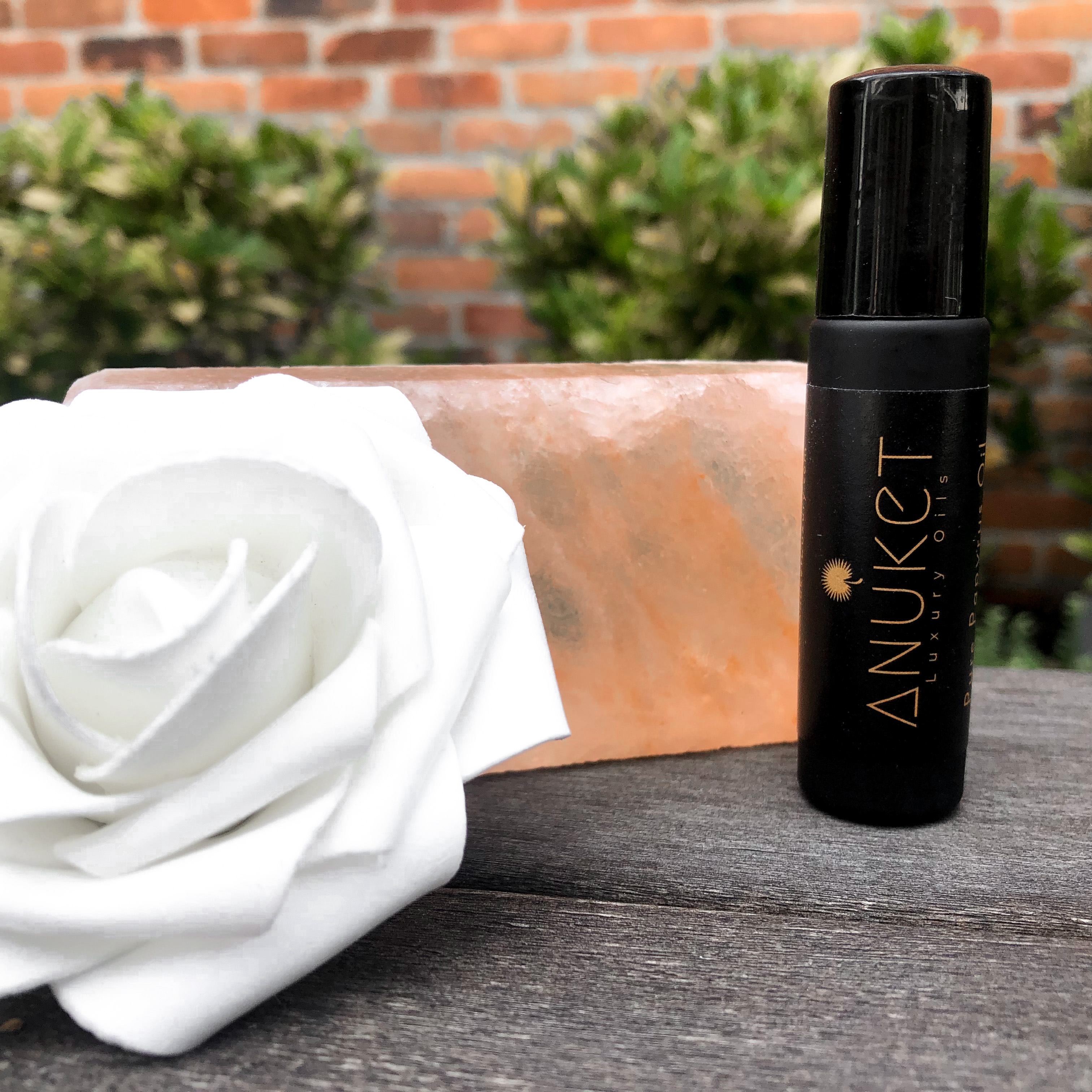 Pure Egyptian Rose Oil, in a black roll on dispenser, on a concrete base with a white rose