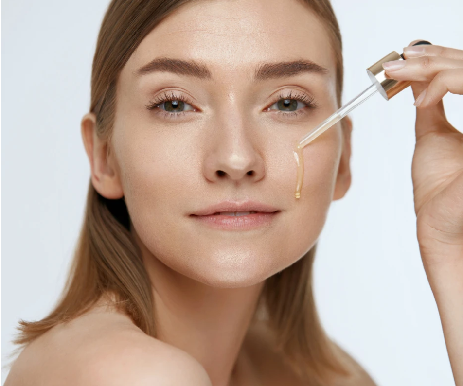 Woman using a skin oil on her face.
