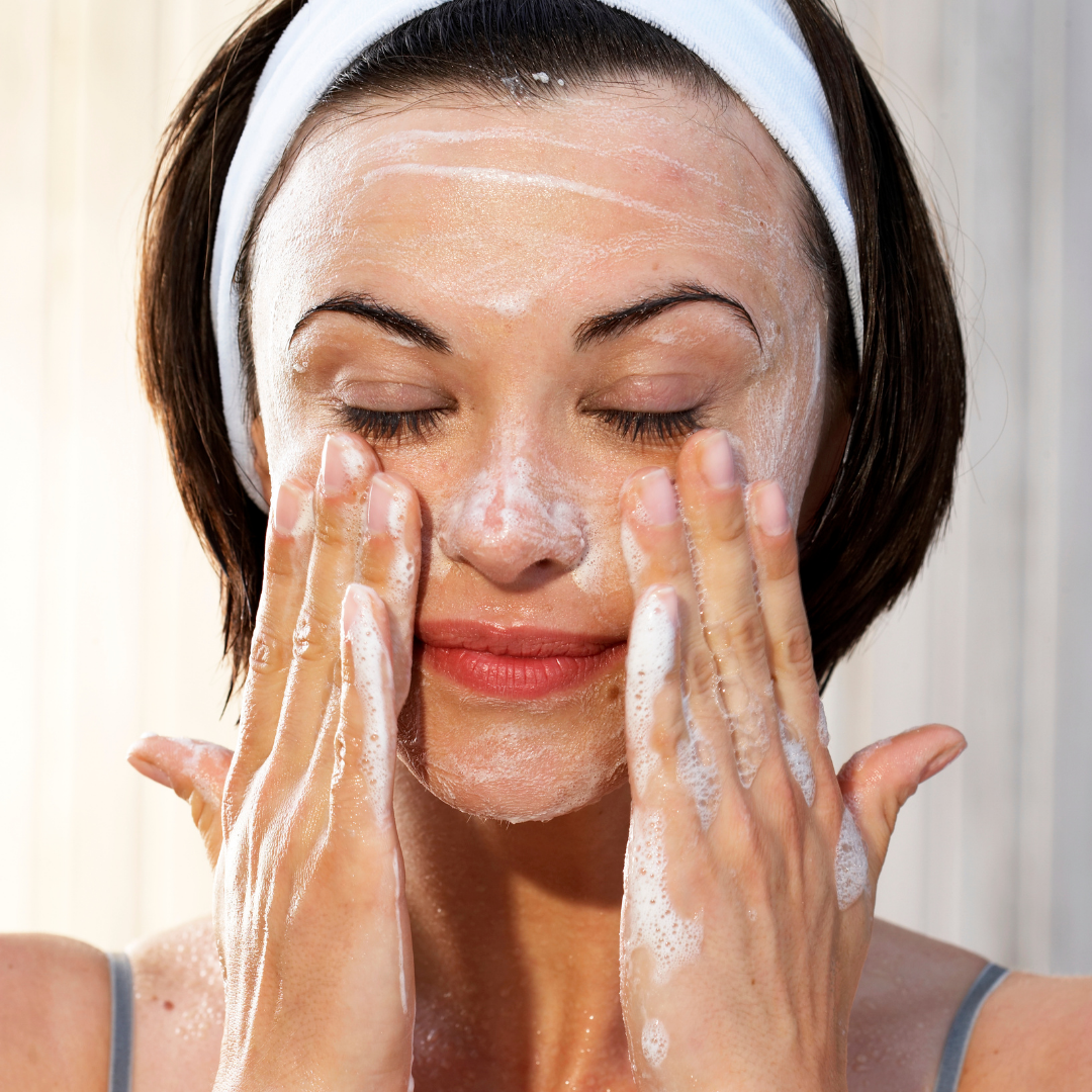 white woman with black hair with head band cleansing her face with foaming cleanser