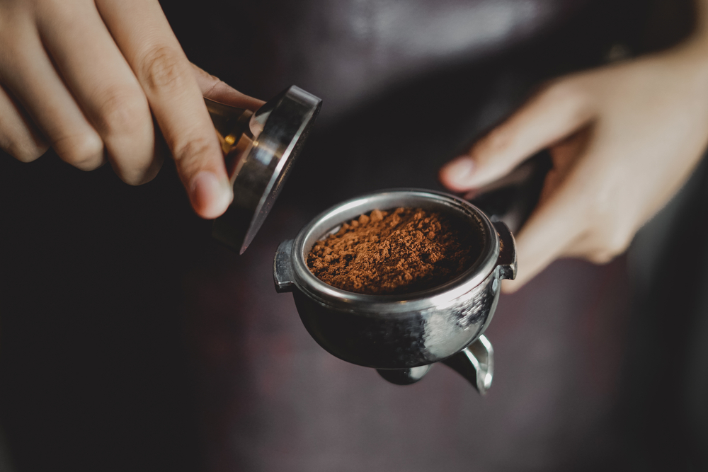 A barista tamping coffee grounds