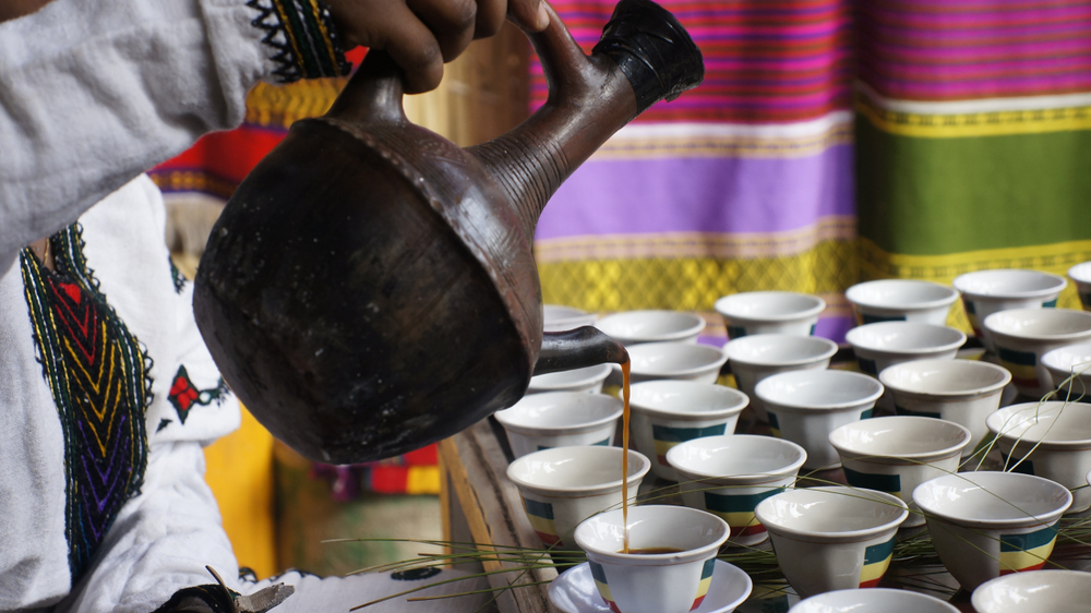 Ethiopians pouring coffee into a cup during a coffee ceremony