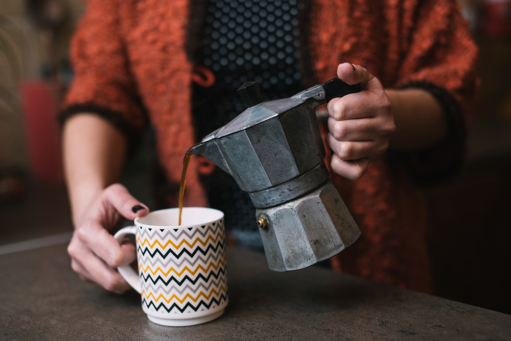 A woman pouring coffee from a Mokapot to a cup