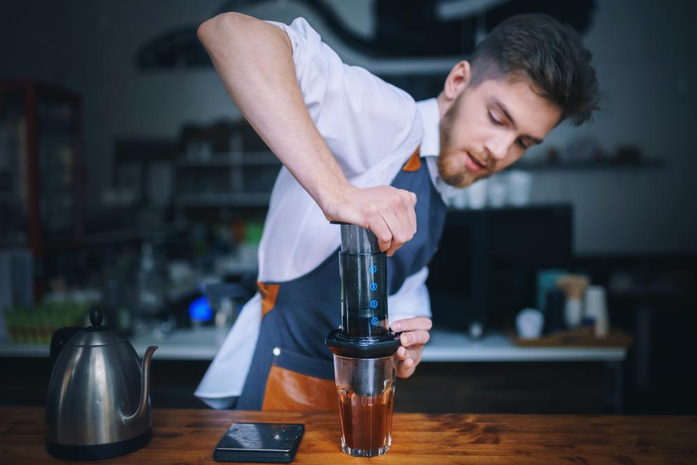 A barista brewing Aeropress coffee
