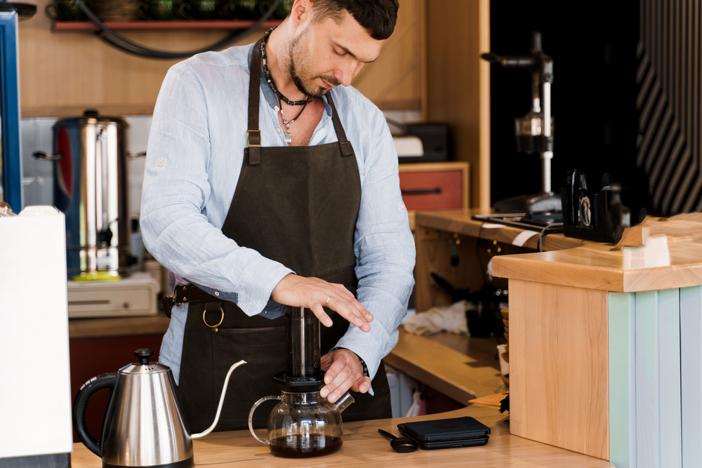 A barista using a French press to brew coffee