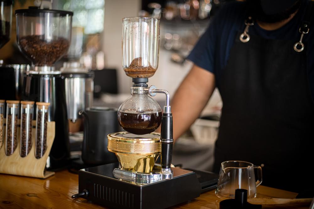 Barista using coffee siphon to brew hot espresso