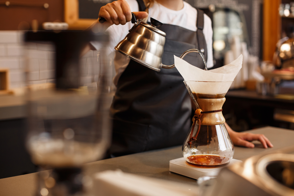 A woman pouring hot water into a chemex to brew coffee