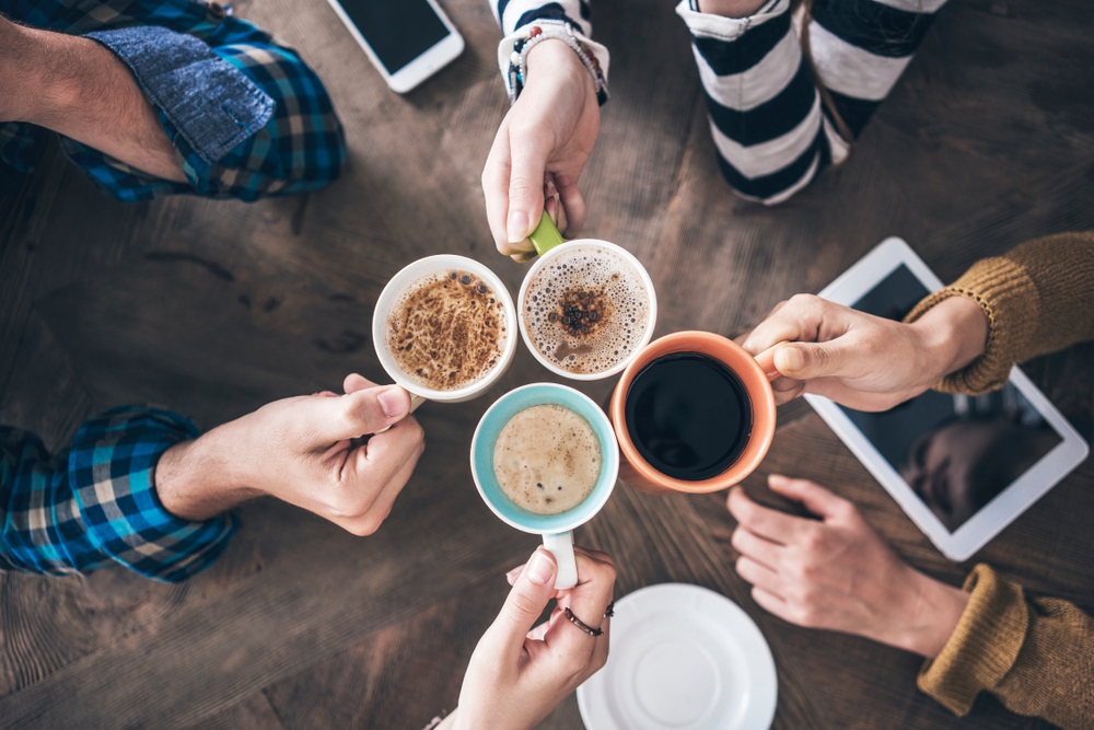 Four people holding their cup of coffee