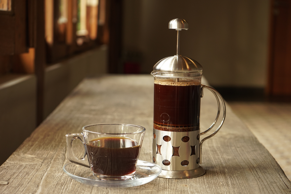 A French press and a mug filled with coffee