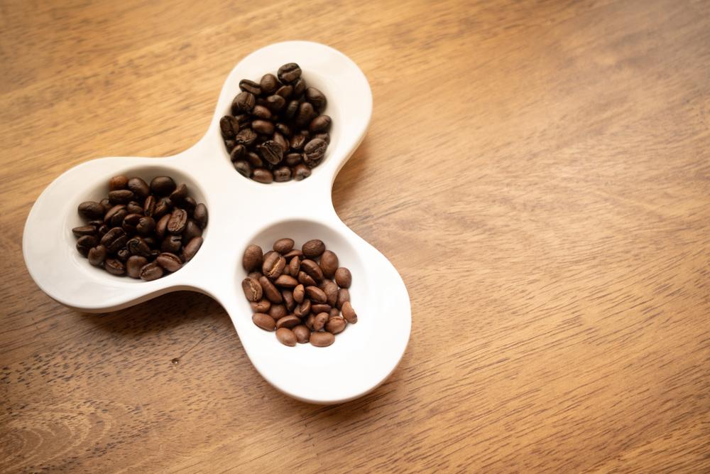 A bowl containing light, medium and dark roast coffee beans
