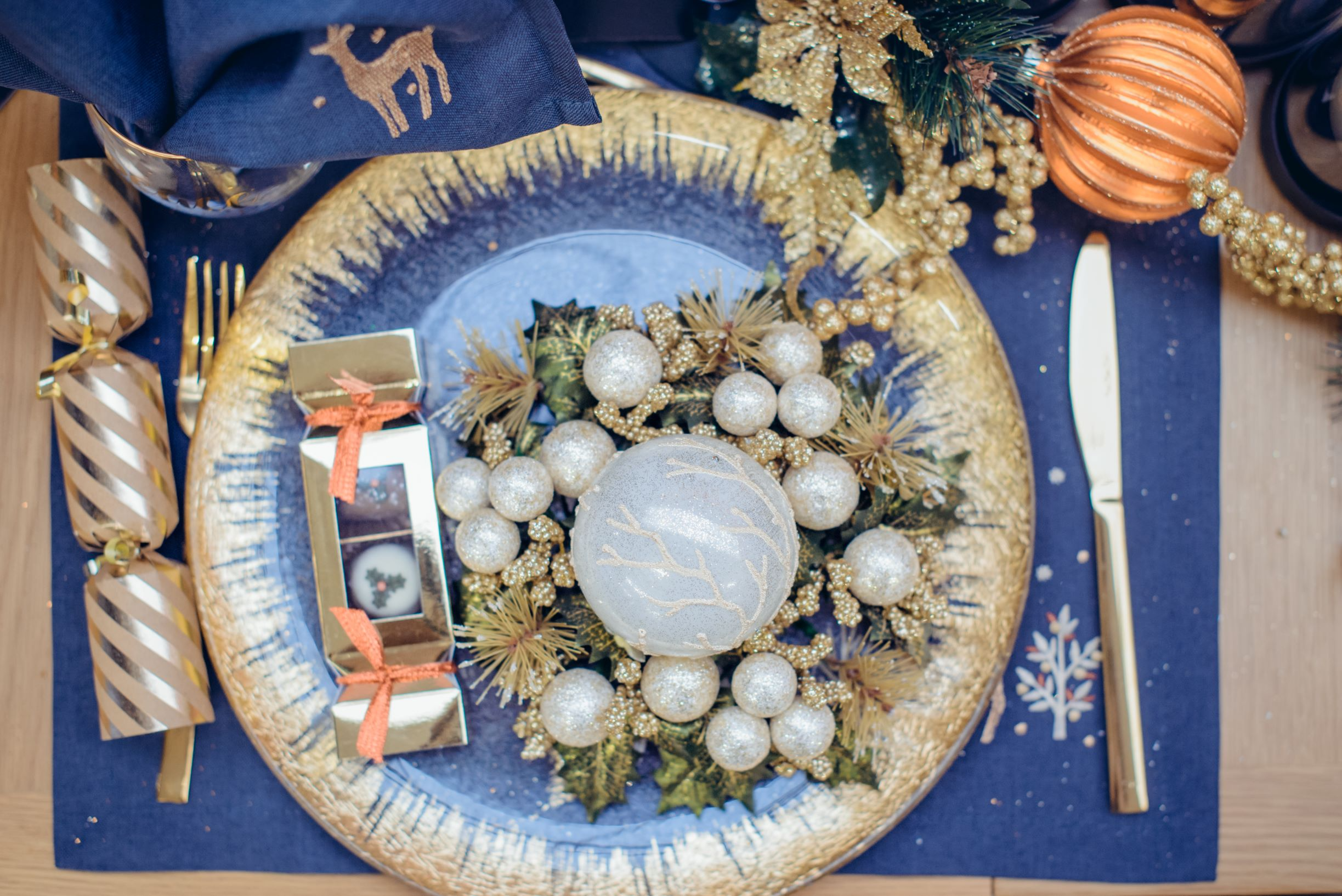 Glam Christmas table setup in blue and gold theme.