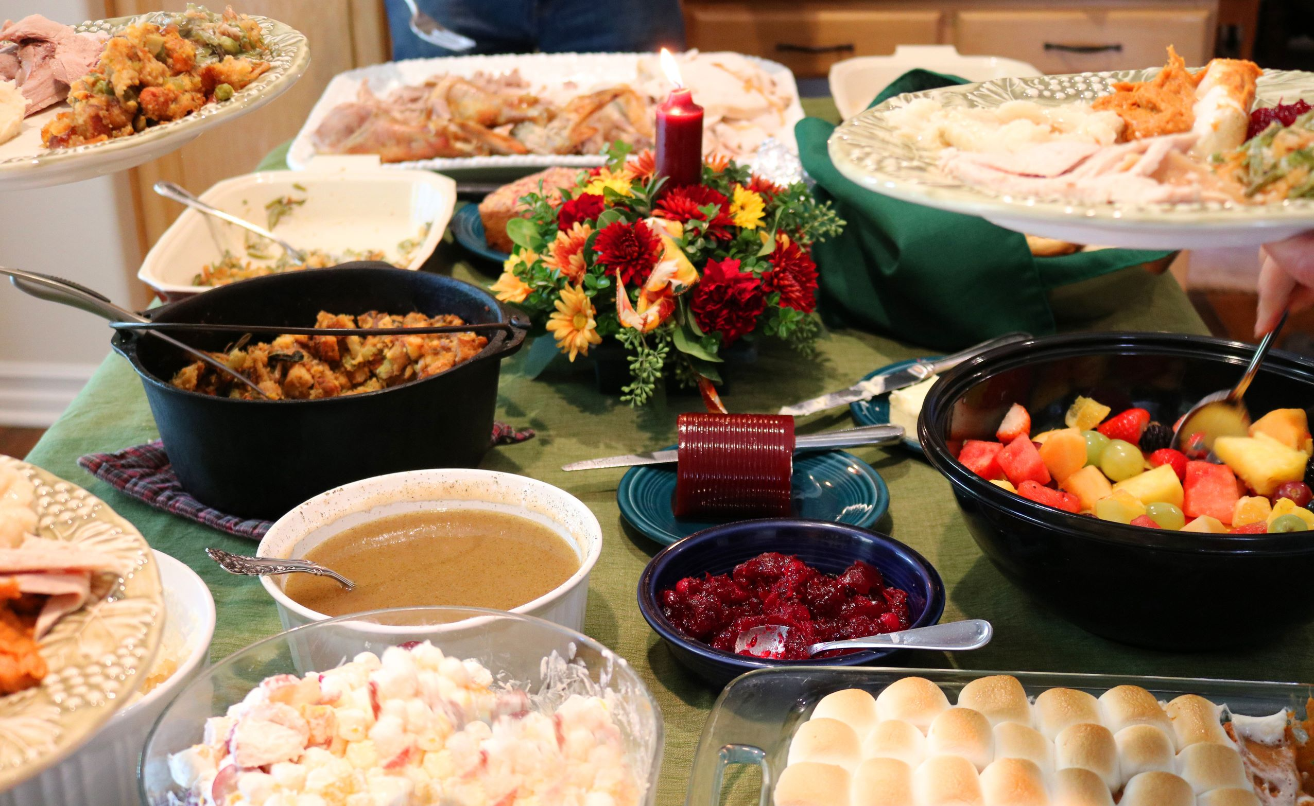 Thanksgiving buffet table with green tablecloth.