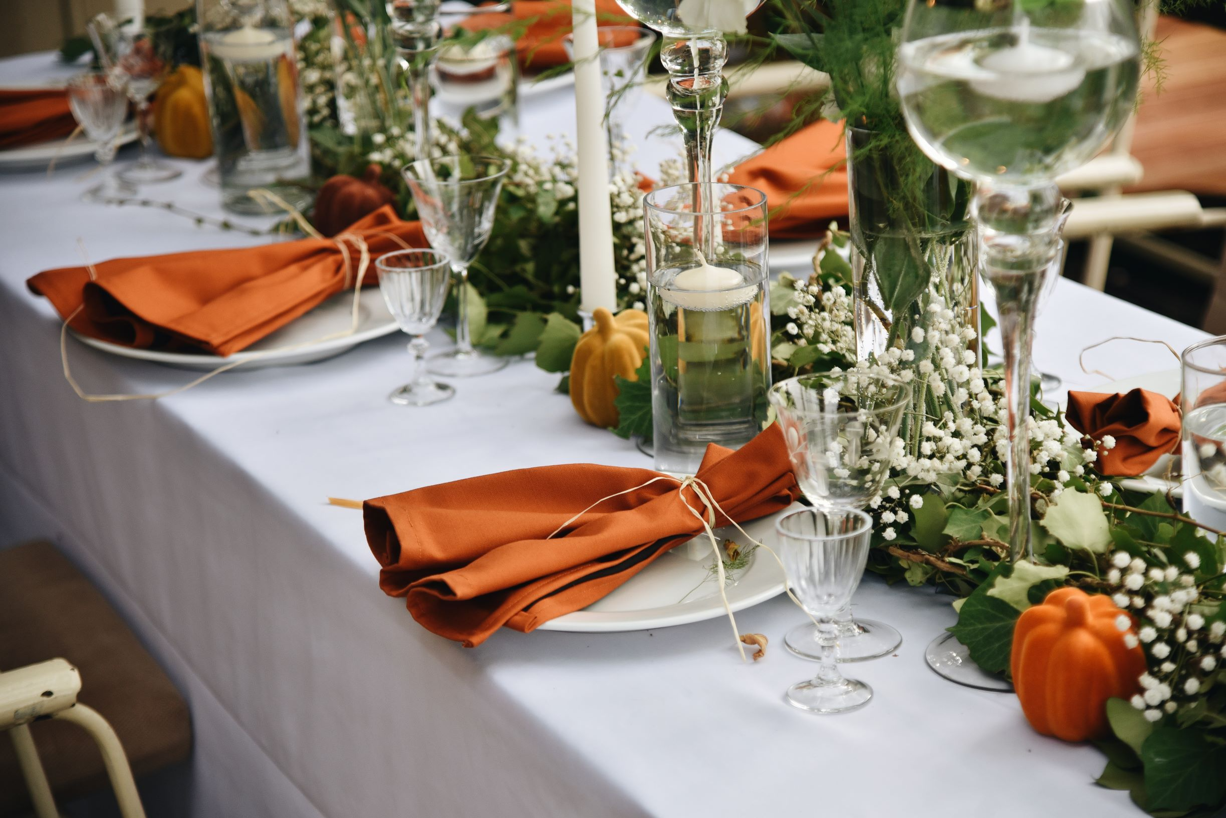 Thanksgiving table in white linens and orange napkins.