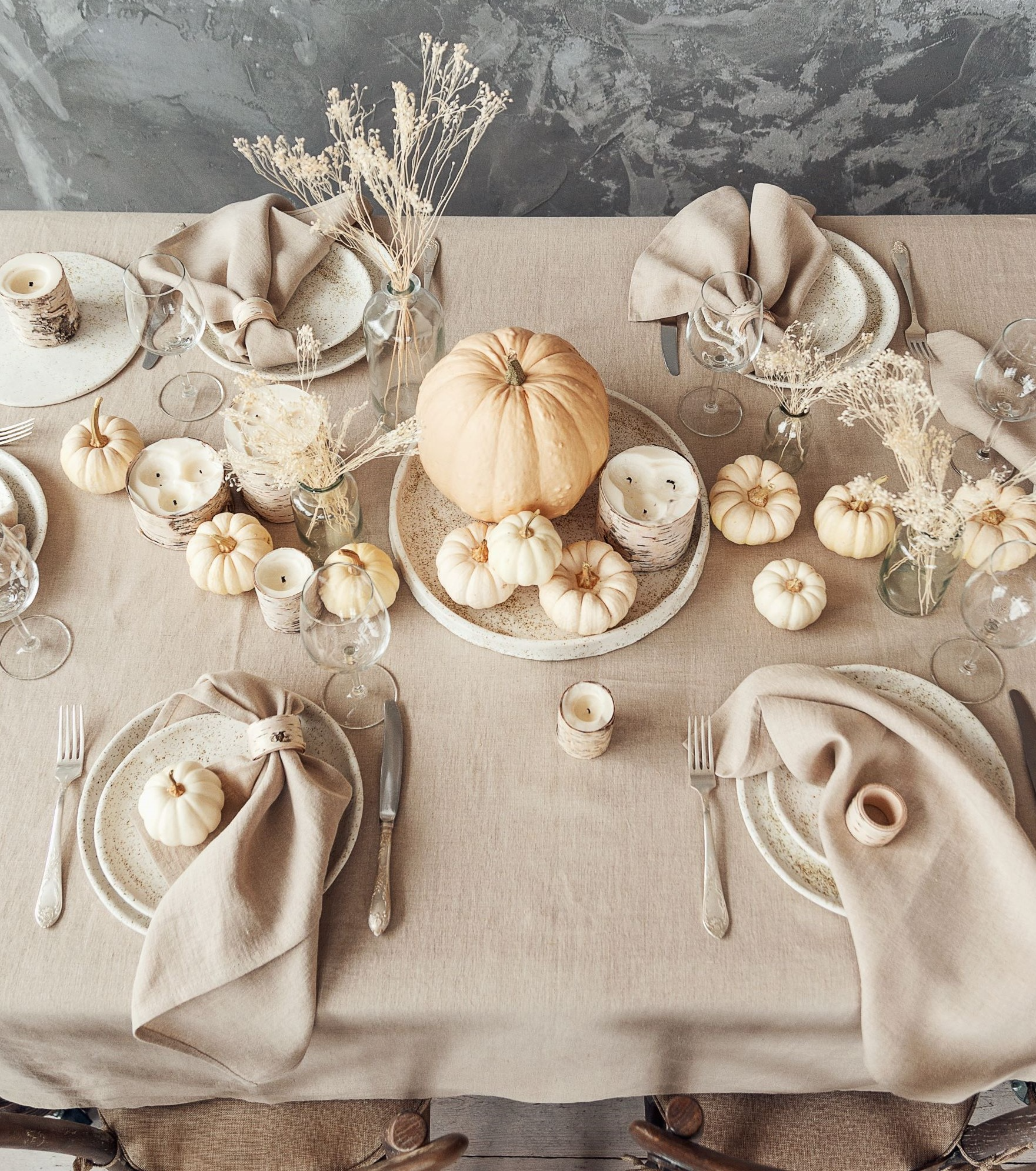 Rustic Thanksgiving table with pumpkin centerpiece.