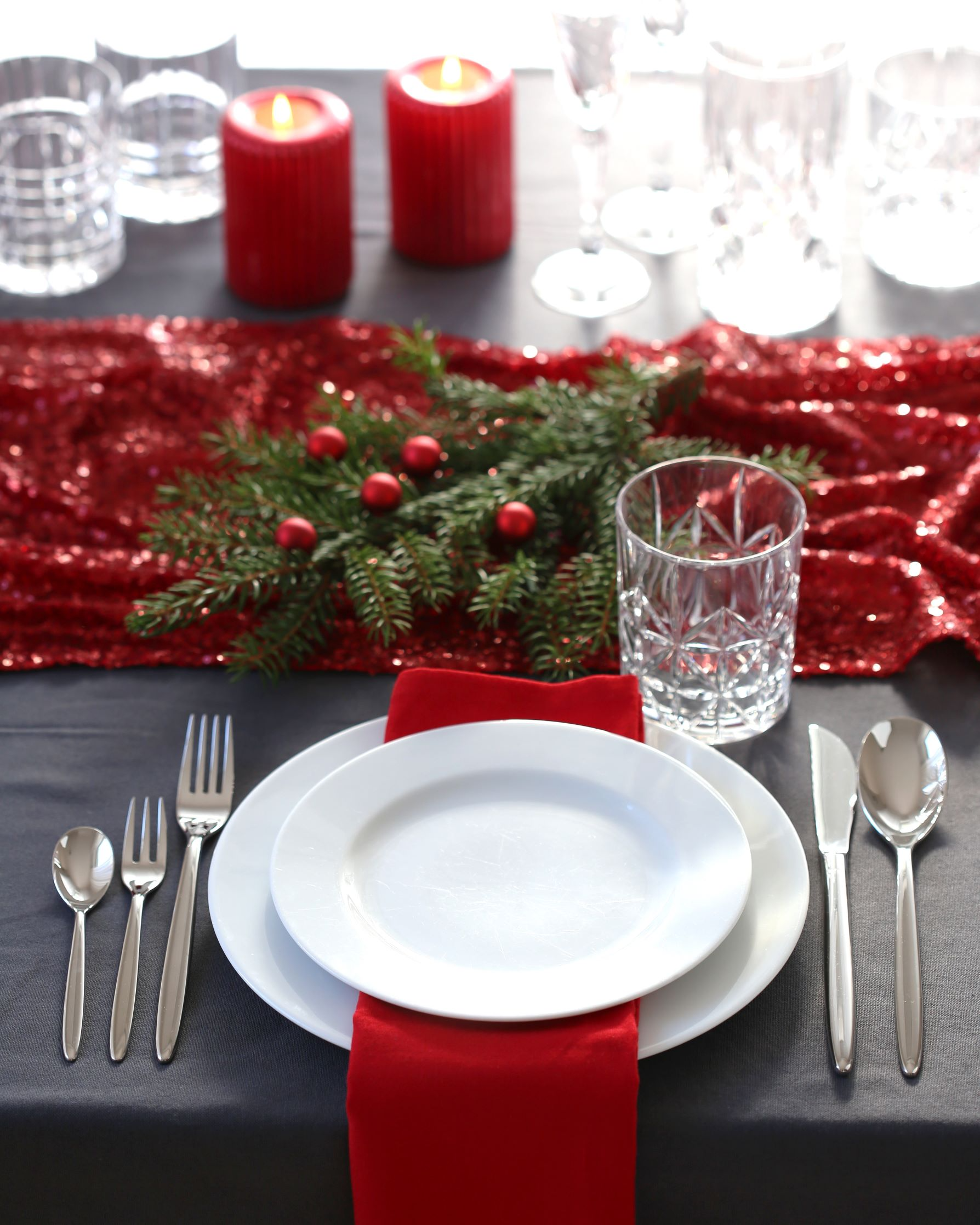 Christmas table featuring red table napkin on a white plate.