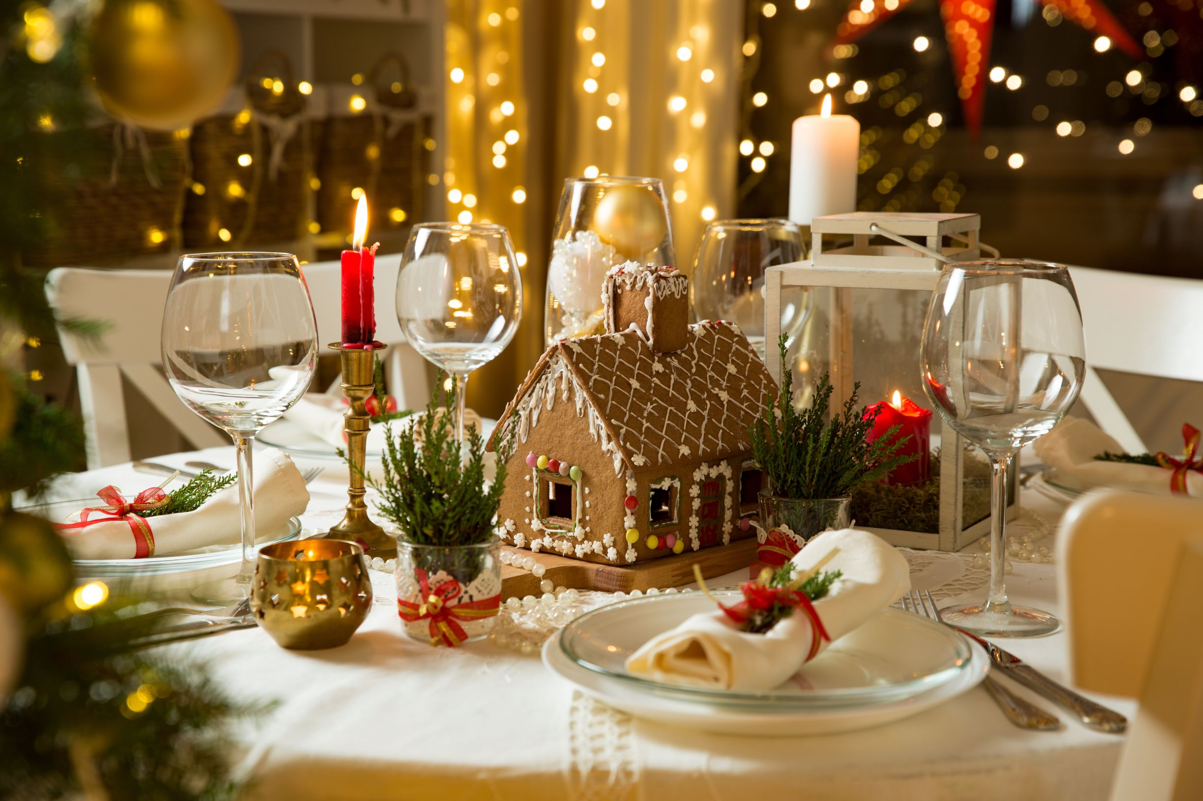 Christmas table with a ginger bread house centerpiece.