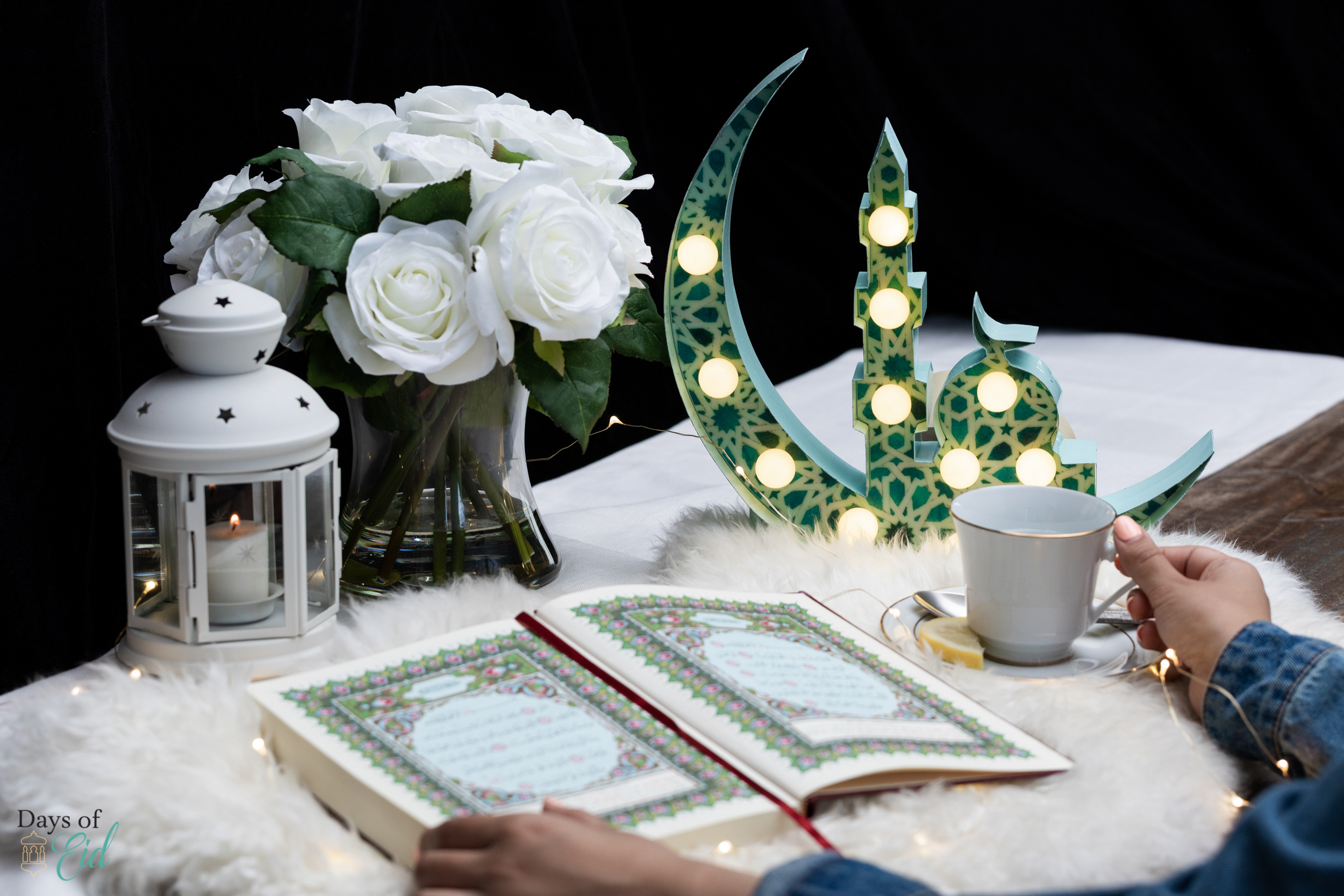 Marquee sign next to an open quran and a cup of tea