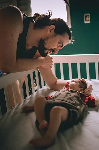 Foto de homem de cabelos compridos amarrados, pele clara, barba e camiseta preta regata fazendo carinho em seu filho bebê no berço.