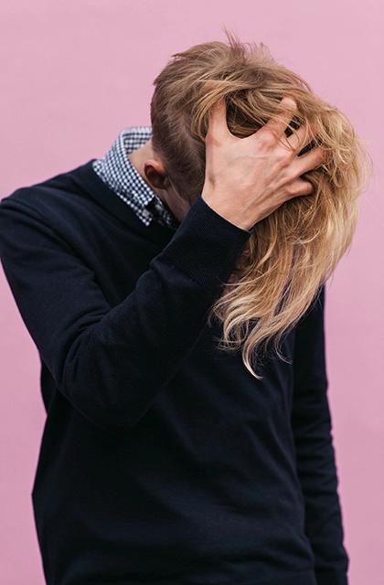 Em artigo sobre caspa, imagem mostra homem loiro de pele clara e cabelos com franja extensa passando a mão na cabeça. Ele veste camisa quadriculada na gola e blusa preta, e os braços cobrem seu rosto.