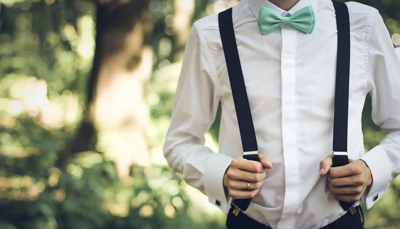 Torso de homem de pele clara, camisa branca, suspensório preto e calça escura. Ele segura o suspensório com cara uma das mãos e usa uma gravata borboleta azul-clara, em alusão às peças de moda masculina que podemos usar do guarda-roupa de nossos pais.
