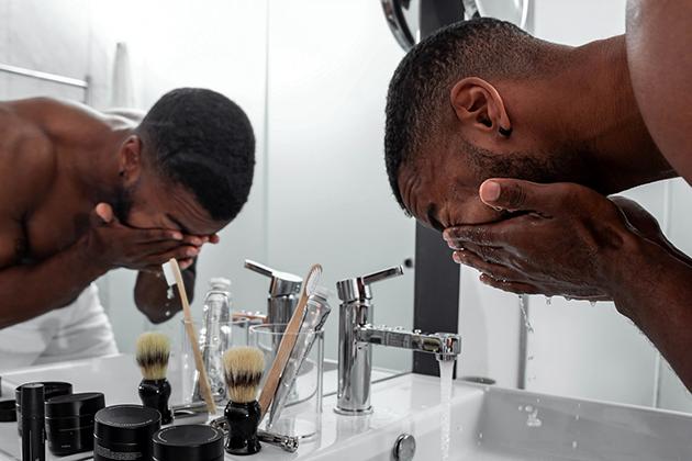 Em artigo sobre hábitos que pioram a oleosidade da pele masculina, imagem mostra homem negro de toalha na parte inferior do corpo lavando o rosto frente a uma pia, no banheiro, com cosméticos na bancada.