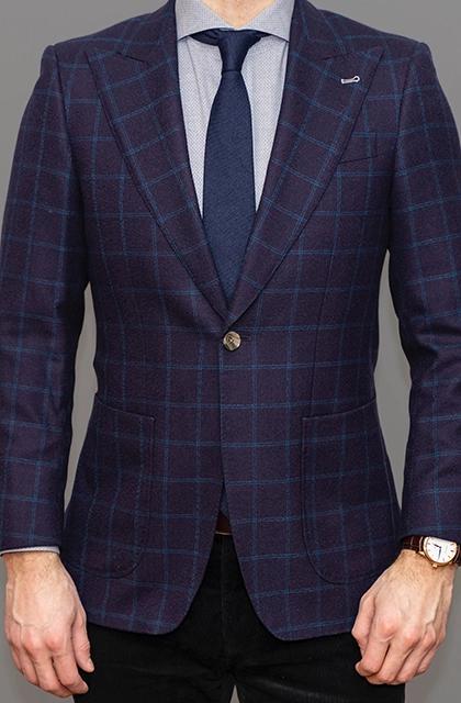 Foto de homem de pele clara, sem rosto, destacando apenas o tronco em que se vê um blazer xadrez de fundo roxo e listras azuis fechado, gravata azul e camisa lilás.