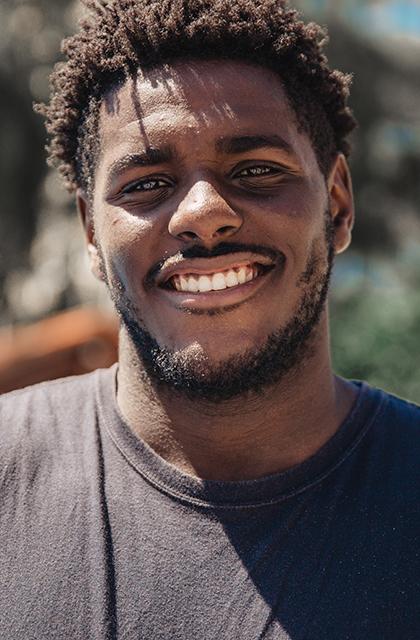 Homem negro, barba rala, camisa cinza-arroxeada sorrindo, parque ao fundo.