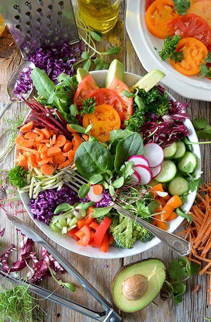 Em artigo sobre falhas na barba, imagem mostra uma tijela branca com garfo e muitos vegetais: cenoura, repolho, brócolis, tomate, pepino. Na mesa ao lado, abacate e mais vegetais.