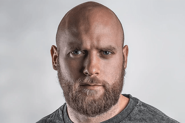Foto de homem careca com barba loira, pele clara, olhos azuis, cabeça completamente raspada com lâmina de barbear. Ele usa camiseta cinza, olha para a câmera em frente a fundo branco.
