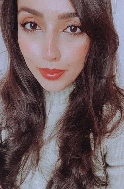 Foto de rosto de Natália de Lucca, analista de produtos da Dr. JONES. Ela tem pele clara, usa batom vermelho e cabelos longos castanhos, com uma blusa cinza.