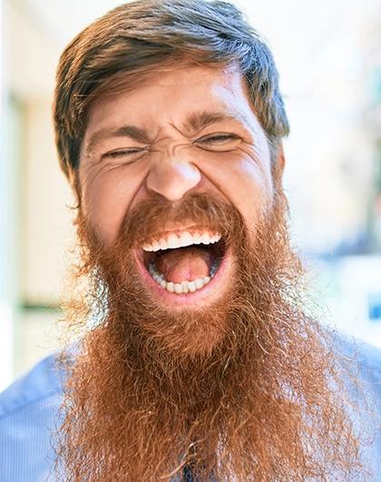 Homem vestindo camisa azul e fazendo careta, como se estivesse gritando, pele clara, cabelos curtos e lisos e barba grande e arrepiada – ambos de fios loiros a ruivos – ilustra artigo sobre coceira na barba.