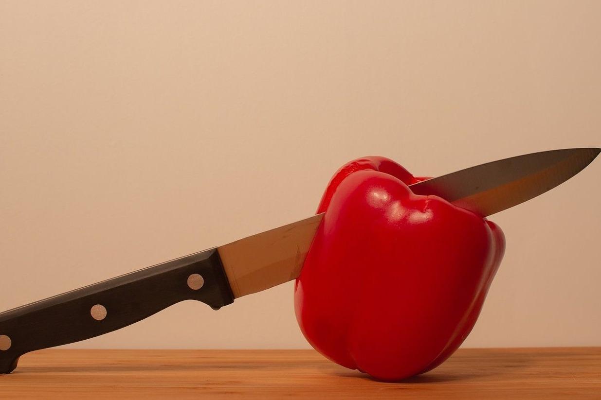 Faca cortando pimentão vermelho sobre mesa de madeira.