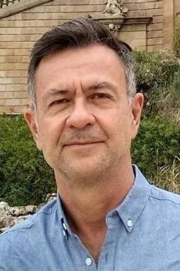 Foto de Wilson Weigl, que é um homem de meia-idade, cabelos grisalhos nas laterais, em frente a uma escadaria e plantas, usando camisa azul-clara.
