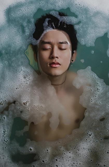 Em artigo sobre falhas na barba, imagem mostra homem oriental mergulhado em piscina com espuma, olhos fechados, rosto fora da água.